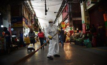Un trabajador barre en el Mercado Central de Abastos en México