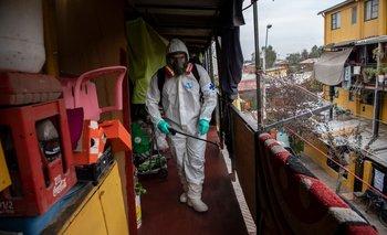 Un trabajador municipal limpia y desinfecta una comunidad de bajos ingresos por la pandemia del coronavirus