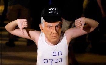 """Manifestante israelí con una máscara de Netanyahu y una frase que dice en hebreo """"el juego se ha terminado"""""""