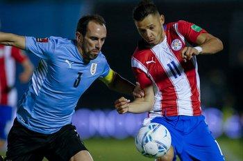 Diego Godín y Ángel Romero pelean por la pelota