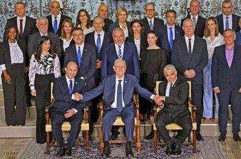 El presidente israelí saliente Reuvin Rivlin, flanqueado por el primer ministro Naftali Bennett y el primer ministro suplente y ministro de Relaciones Exteriores Yair Lapid durante una foto con el nuevo gobierno de coalición, en la residencia del presidente en Jerusalén, el 14 de junio de 2021