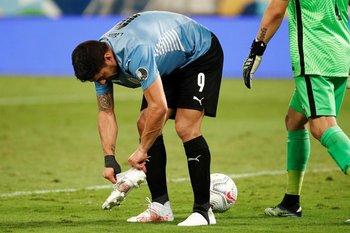 Luis Suárez se acomoda el zapato en el área chilena