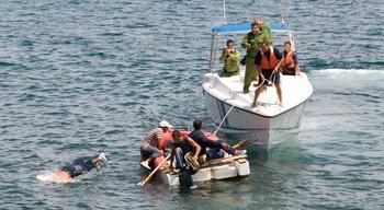En esta imagen de archivo, guardacostas cubanos ordenan a los aspirantes a emigrados cubanos en un bote casero que regresen a la costa luego de que su intento de escapar de la isla fuera frustrado por las corrientes marinas