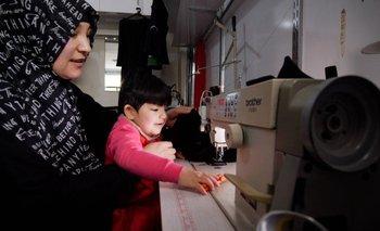 BBC Kalbinur, fotografiada con su hijo Merziye, cose ropa para mantener a su familia