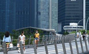 La gente camina a lo largo de un puente peatonal en el distrito financiero de Singapur, el 25 de junio de 2021
