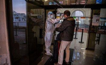 Un funcionario de Buquebús le toma la temperatura a un pasajero