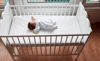 Bebé durmiendo solo en una cuna en una habitación.