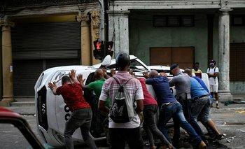 La gente empuja un automóvil volcado en la calle en el marco de una manifestación contra el presidente cubano.