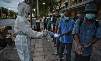 Un trabajador desinfecta a personas que viven en las calles de Bangkok para prevenir el crecimiento de los contagios de coronavirus