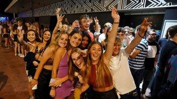 Clientes en la cola para entrar en un club nocturno en Brighton, Inglaterra, celebran el fin de las restricciones.