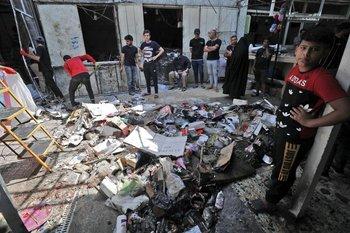 Ciudadanos iraquíes inspeccionan el lugar de la explosión