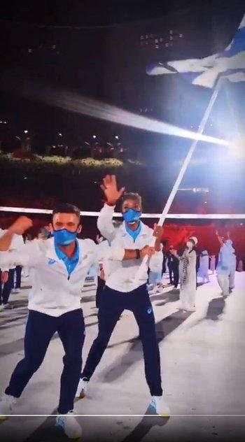 Bruno Cetraro y Déborah Rodríguez con la bandera uruguaya en pleno desfile de la delegación en el Estadio Olímpico