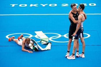 El noruego Kristian Blummenfelt celebra la medalla de oro sobre el suelo de la competencia de triatlón, mientras que Alex Yee, del equipo de Reino Unido y quien obtuvo la plata, se abraza a Hayden Wilde, de Nueva Zelanda y ganador del bronce
