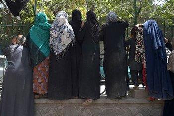 Las mujeres afganas desplazadas internamente, que huyeron de la provincia del norte debido a la batalla entre los talibanes y las fuerzas de seguridad afganas, se reúnen para recibir alimentos gratuitos distribuidos por hombres chiítas