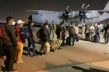 Personas hacen fila para abordar un avión de transporte militar francés en el aeropuerto de Kabul el 17 de agosto de 2021, para ser evacuados de Afganistán después de la impresionante toma militar de país parte de los talibanes.