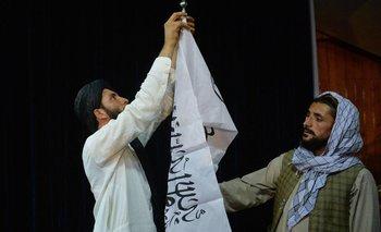 Los hombres ajustan la bandera de los talibanes antes de la llegada del portavoz de los talibanes Zabihullah Mujahid (invisible) para dirigirse a la primera conferencia de prensa en Kabul el 17 de agosto de 2021.