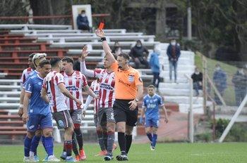 Diego Riveiro le muestra la tarjeta roja a Bergessio por su falta al final del partido