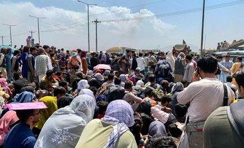 Afganos se reúnen a lo largo de una carretera mientras esperan para abordar un en un aeropuerto en Kabul, el 20 de agosto de 2021