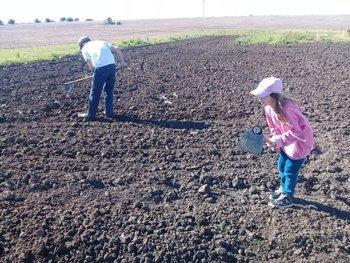 Gustavo Rostagnol, joven productor rural y su sobrina Emma, quien lo acompaña de a ratos en la huerta.