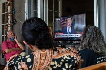 Familias militares, incluido un veterano posterior al 11 de septiembre que sirvió en Afganistán y la madre de un infante y marina que salió del aeropuerto la semana pasada se reúnen para ver el discurso de Biden anunciando que todas las tropas están fuera de servicio