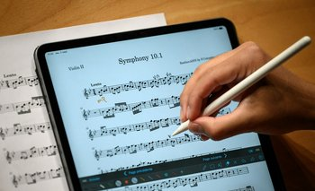 Un miembro de la orquesta Nexus anota una partitura musical en su tableta durante un ensayo en Lausana el 2 de septiembre de 2021.