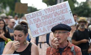 """Un hombre sostiene un cartel que dice """"Electos, traidores de mi confianza. Indigno del cargo"""" durante una manifestación contra el pase de salud obligatorio Covid-19 para acceder a la mayor parte del espacio público, en Nantes."""