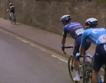 El niño pedalea por la vereda marcándole el ritmo a los profesionales van por la calle en el Tour Británico