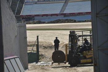 Los operarios y maquinarias en plena tarea, la base de arena que tiene la cancha del Estadio y el primer rollo de césped colocado