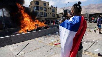 Un ciudadano toma una imagen de la quema de ropa y pertenencias de los migrantes que han llegado a Iquique en los últimos meses.
