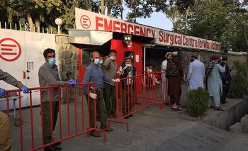 Los miembros del personal médico afgano se encuentran en la entrada de un hospital mientras esperan recibir a las víctimas de una explosión en Kabul.