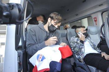 Matías Viña firma una camiseta de Nacional mientras espera en la camioneta que lo trasladará al Complejo de la AUF