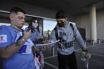 Suárez pasa la puerta del aeropuerto y lo esperan hinchas para tener su autógrafo