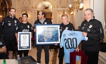 Diego Godín, los neutrales Matías Pérez, Fernando Sosa y Julian Moreno, junto a Tabárez y sus premios.
