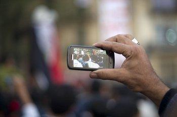 En esta foto de archivo tomada el 24 de noviembre de 2011, un hombre usa su teléfono celular para registrar la actividad de otros manifestantes antigubernamentales durante una manifestación masiva en la plaza Tahrir de El Cairo. Las redes sociales y los teléfonos inteligentes dieron brevemente a los jóvenes manifestantes de la Primavera Árabe una ventaja tecnológica que les permitió derrocar dictaduras envejecidas a medida que su espíritu revolucionario se volvía viral.