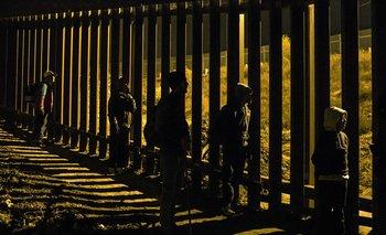 Migrantes en la frontera de Tijuana con Estados Unidos, el pasado sábado, mirando desde el lado mexicano a agentes de control del otro lado de la valla