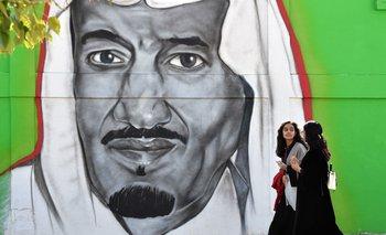 Mujeres saudíes caminan frente a un mural del rey Salman bin Abdulaziz en Riad