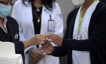 Una trabajadora de la salud pasa una jeringa de Pfizer a su compañera