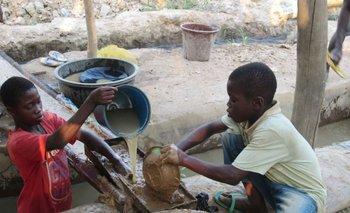 Niños de 12 y 9 años enseñan cómo lavan la tierra y separan el oro.