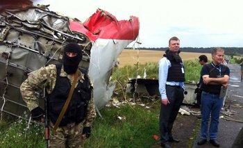Observadores de la OSCE en el lugar del accidente, custodiado por un miliciano prorruso.<br>