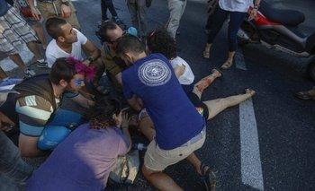 Varias personas tratan de ayudar a una de las seis personas apuñaladas mientras participaban en la Marcha del Orgullo Gay hoy en Jerusalén, Israel.