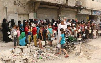 Sirios desplazados hacen fila para conseguir comida, en la zona de Alepo controlada por los rebeldes.<br>