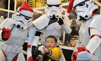 Fans de Star Wars disfrazados de stormtroopers posan con un niño durante una exhibición de juguetes en Taipei, Taiwán