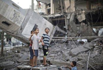 Niños en los escombros de una mezquita derribada en Gaza por bombardeos.
