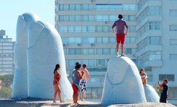 Un hombre parado sobre uno de los dedos de la escultura ubicada en la Brava de Punta del Este