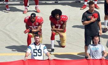 Kaepernick (7) y su gesto junto a Eric Reid (35) durante el himno