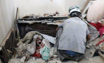 <p>Voluntarios de protección civil de Siria los cuerpos de entre los escombros de un edificio tras un ataque.</p><p></p>