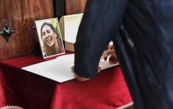 Un hombre firma en el libro de condolencias durante el funeral de María Villar