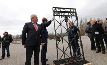 """El ministro de educación y asuntos culturales de Bavaria, Ludwig Spaenle, frente a la puerta con el eslogan """"El trabajo los hará libres""""."""