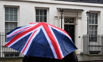 Un periodista se cubre con un paraguas frente al 11 de Downing Street