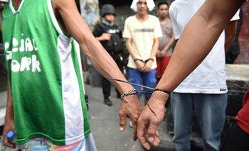 Un agente de la Agencia de Lucha contra las Drogas de Filipinas acompaña a sospechosos en Filipinas